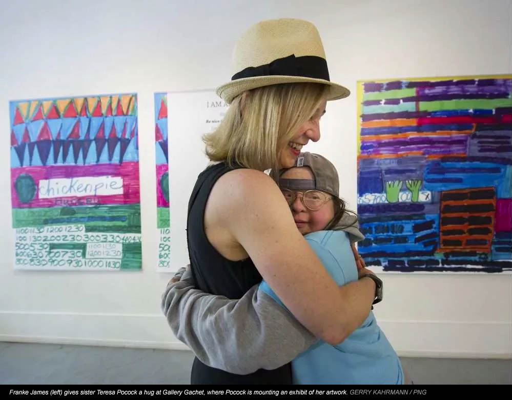 Franke James (left) gives sister Teresa Pocock a hug at Gallery Gachet, where Pocock is mounting an exhibit of her artwork. GERRY KAHRMANN / PNG